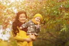 Famiglia nel parco soleggiato di autunno fotografia stock