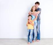 Famiglia nell'abbraccio vicino alla parete Fotografia Stock