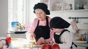Famiglia nella cucina che produce i dessert Una donna anziana che taglia la banana stock footage