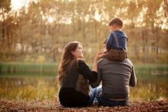 Famiglia nella foresta di autunno, vista dalla parte posteriore Immagini Stock Libere da Diritti