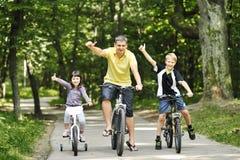 Famiglia nella sosta sulle biciclette Fotografia Stock Libera da Diritti