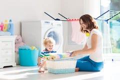 Famiglia nella stanza di lavanderia con la lavatrice fotografie stock libere da diritti