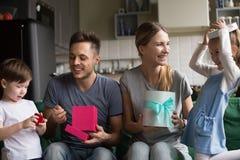 Famiglia numerosa felice che disimballa i regali con il figlio e la figlia fotografia stock