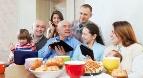 Famiglia o amici con gli apparecchi elettronici Fotografia Stock