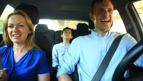 Famiglia, papà della mamma e guida del figlio in automobile, cantano le canzoni con l'intera famiglia video d archivio