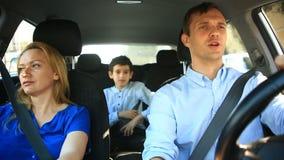 Famiglia, papà della mamma e guida del figlio in automobile, cantano le canzoni con l'intera famiglia archivi video