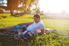 Famiglia, papà felice e figlio riposanti nella sera al tramonto Fotografia Stock Libera da Diritti