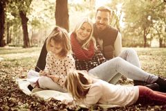 Famiglia in parco insieme e libro da colorare delle bambine Immagine Stock Libera da Diritti