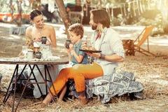 Famiglia piacevole positiva che mangia insieme alimento sano fotografie stock libere da diritti