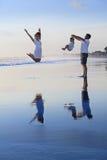 Famiglia positiva divertendosi sulla spiaggia nera del mare della sabbia immagine stock libera da diritti
