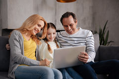 Famiglia positiva facendo uso dell'aggeggio elettronico a casa Fotografia Stock Libera da Diritti