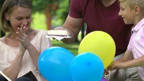 Famiglia preoccupantesi che si congratula mummia sul compleanno, festa di famiglia di sorpresa all'aperto stock footage