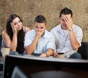 Famiglia rabbrividente alla televisione immagine stock