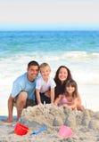 Famiglia radiante alla spiaggia Fotografie Stock Libere da Diritti