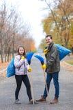 Famiglia, ragazza con il papà pulito nel parco di autunno, supporto con le borse di immondizia e scope della tenuta immagine stock