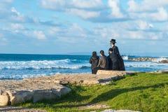 Famiglia religiosa dell'ebreo che si siede sulla costa del mar Mediterraneo in Israele e che guarda le onde Spiaggia di tramonto, Immagini Stock Libere da Diritti