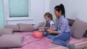 Famiglia rilassata con le patatine fritte ed il gioco del PC video d archivio