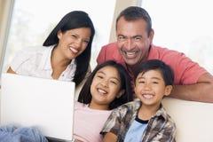 Famiglia in salone con il computer portatile immagine stock