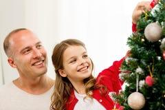 Famiglia sorridente che decora l'albero di Natale a casa Immagini Stock