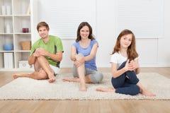 Famiglia sorridente che esegue yoga sulla coperta Immagini Stock Libere da Diritti
