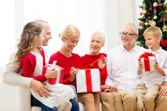 Famiglia sorridente con i regali a casa Immagini Stock