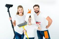 Famiglia sorridente con i vari rifornimenti di pulizia su bianco immagini stock