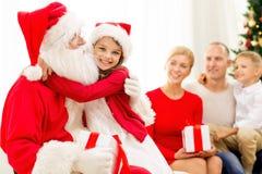 Famiglia sorridente con il Babbo Natale ed i regali a casa Fotografie Stock Libere da Diritti