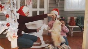 Famiglia sorridente con il derivato ed il cane sul portico con l'albero di Natale e la decorazione stock footage