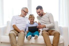 Famiglia sorridente con il pc della compressa a casa Immagini Stock Libere da Diritti