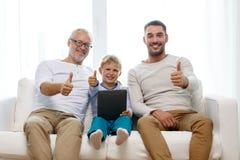 Famiglia sorridente con il pc della compressa a casa Fotografia Stock Libera da Diritti