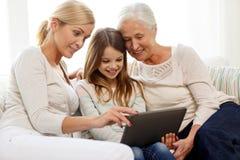 Famiglia sorridente con il pc della compressa a casa Immagine Stock Libera da Diritti