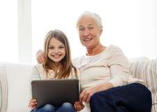 Famiglia sorridente con il pc della compressa a casa Immagine Stock
