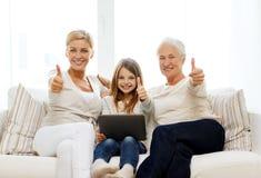 Famiglia sorridente con il pc della compressa a casa Fotografia Stock