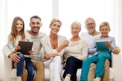 Famiglia sorridente con il pc della compressa a casa Fotografie Stock