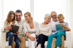 Famiglia sorridente con il pc della compressa a casa Fotografie Stock Libere da Diritti