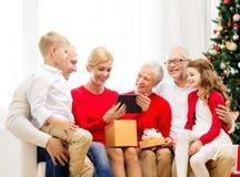 Famiglia sorridente con il pc della compressa ed il contenitore di regalo a casa Fotografia Stock