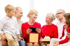 Famiglia sorridente con il pc della compressa ed il contenitore di regalo a casa Immagini Stock Libere da Diritti