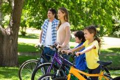 Famiglia sorridente con le loro bici Fotografia Stock Libera da Diritti