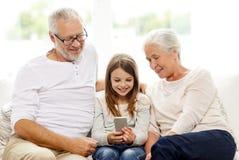 Famiglia sorridente con lo smartphone a casa Immagine Stock Libera da Diritti