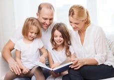 Famiglia sorridente e due bambine con il libro Fotografia Stock