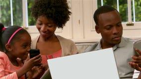 Famiglia sorridente facendo uso di tecnologia sul sofà stock footage