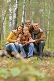 Famiglia sorridente felice nella seduta della foresta di autunno Immagine Stock Libera da Diritti