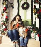 Famiglia sorridente felice sul Natale alla casa con i regali, la giovane madre ed il piccolo figlio in cappello rosso di Santa, f fotografie stock libere da diritti