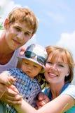 Famiglia sorridente felice sulla priorità bassa del cielo blu Immagini Stock Libere da Diritti