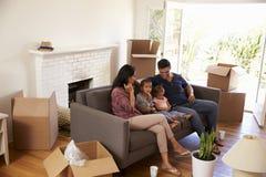 Famiglia su Sofa Taking una rottura dal disimballaggio della TV di sorveglianza immagini stock