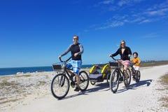 Famiglia su un giro della bicicletta della spiaggia insieme Immagine Stock