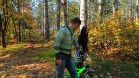 Famiglia su una passeggiata con una bicicletta nel movimento lento della foresta di autunno archivi video