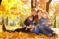 Famiglia sui fogli di autunno fotografia stock libera da diritti