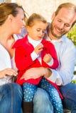 Famiglia sul banco del giardino davanti alla casa Fotografie Stock Libere da Diritti