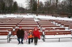 Famiglia sul banco di inverno Immagini Stock Libere da Diritti